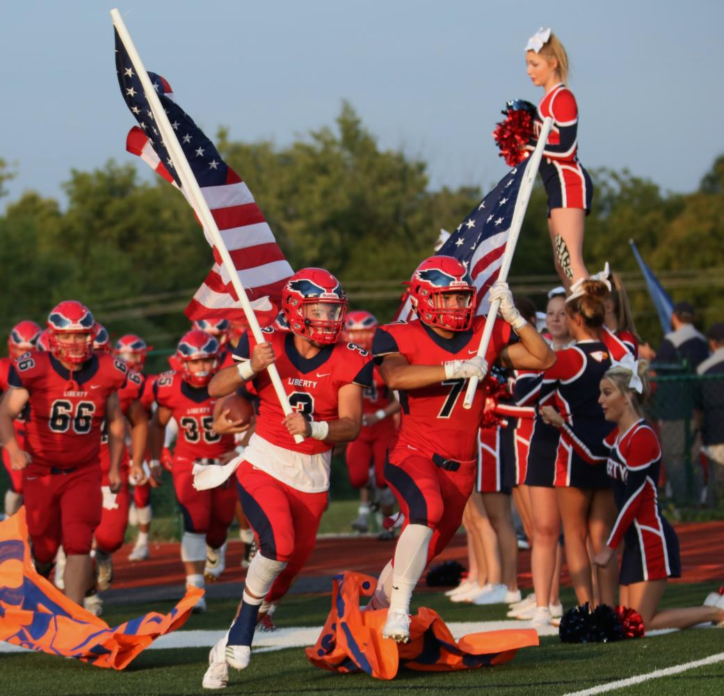 Every home game the football players run through a sign with the flags for school pride and spirit