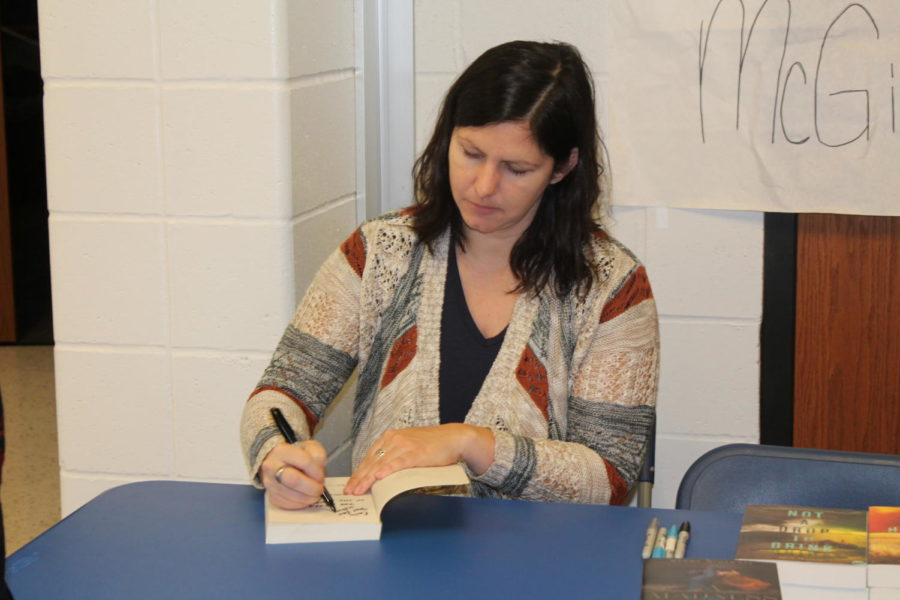 Mindy+McGinnis+signs+one+of+her+books+for+an+LHS+student.