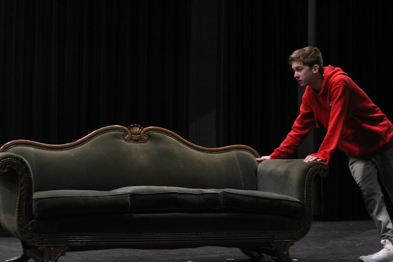 Freshman Evan Mantz moves a set piece onto the stage.