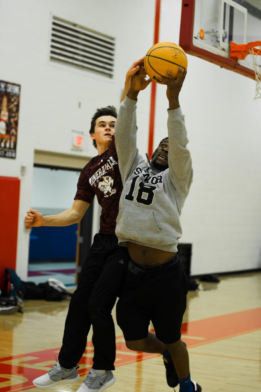 Andrew Fey and Corey Williams play basketball in a P.E. class.