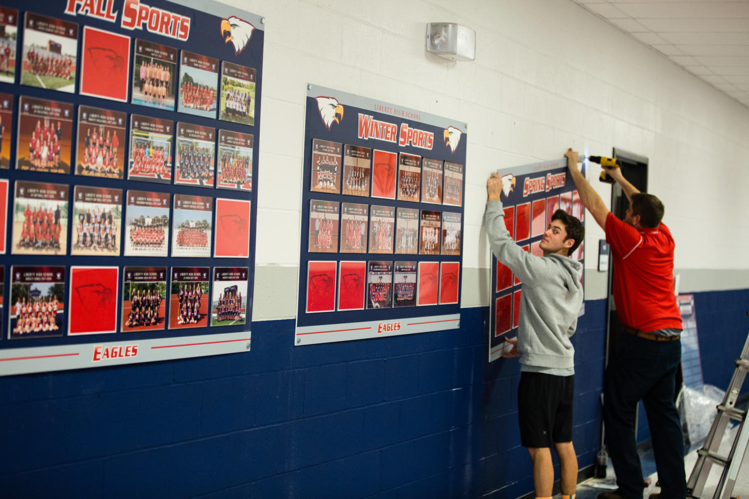 Mr. Labrot and senior Mike Rybak put up one of the boards for the Champions Hallway.