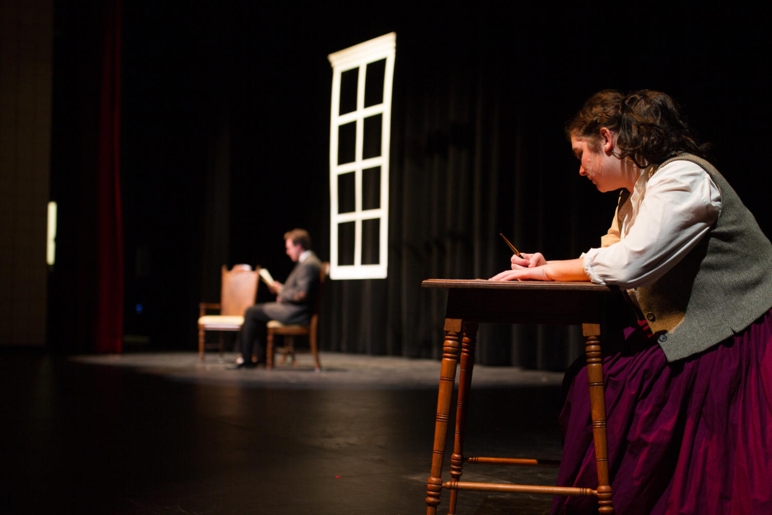 Senior Julia Wolz plays Jo March in Little Women.  In this scene of Act II, Jo writes a letter to junior Cameron Jones' character Professor Bhaer.