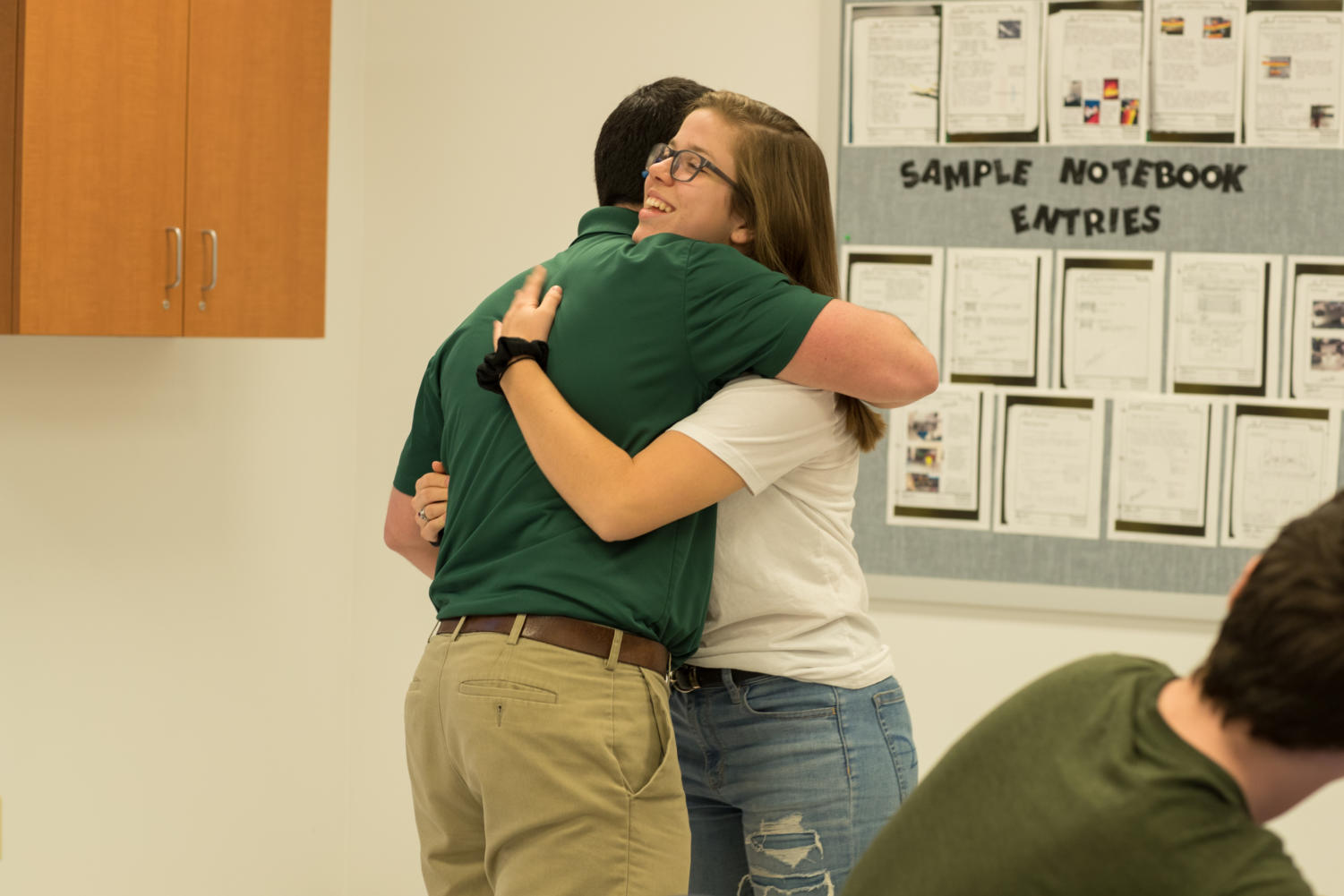 Mr. Peggs hugs Key Club president Mikayla Bowman after receiving the money that was fundraised.