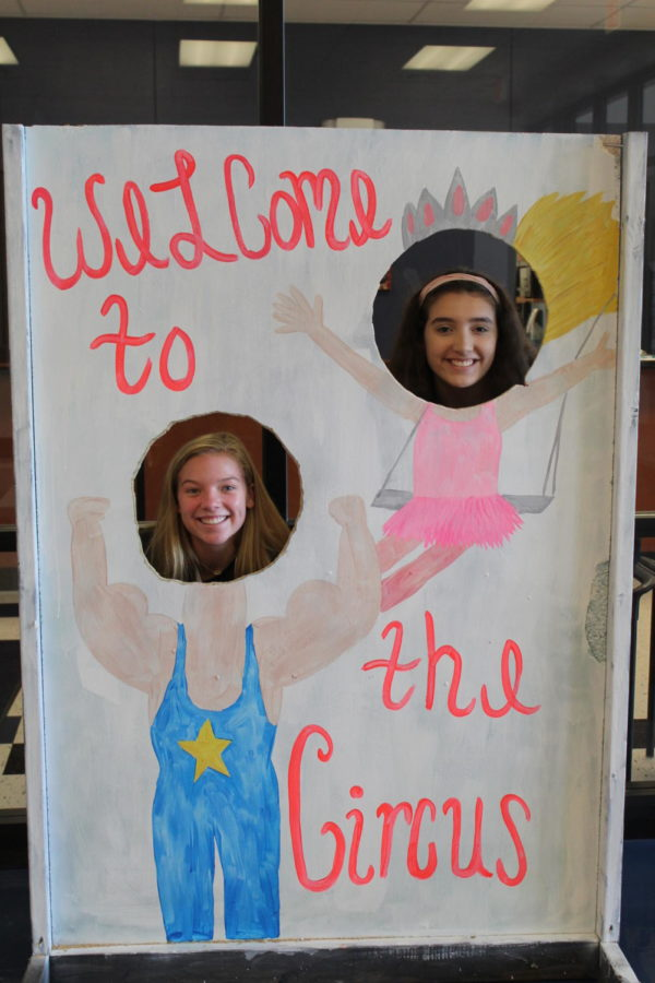 Sophomores Katie Swanson and Lola Cadice pose behind a sign all set up for Libertys 2018 homecoming theme; Welcome to the Circus.