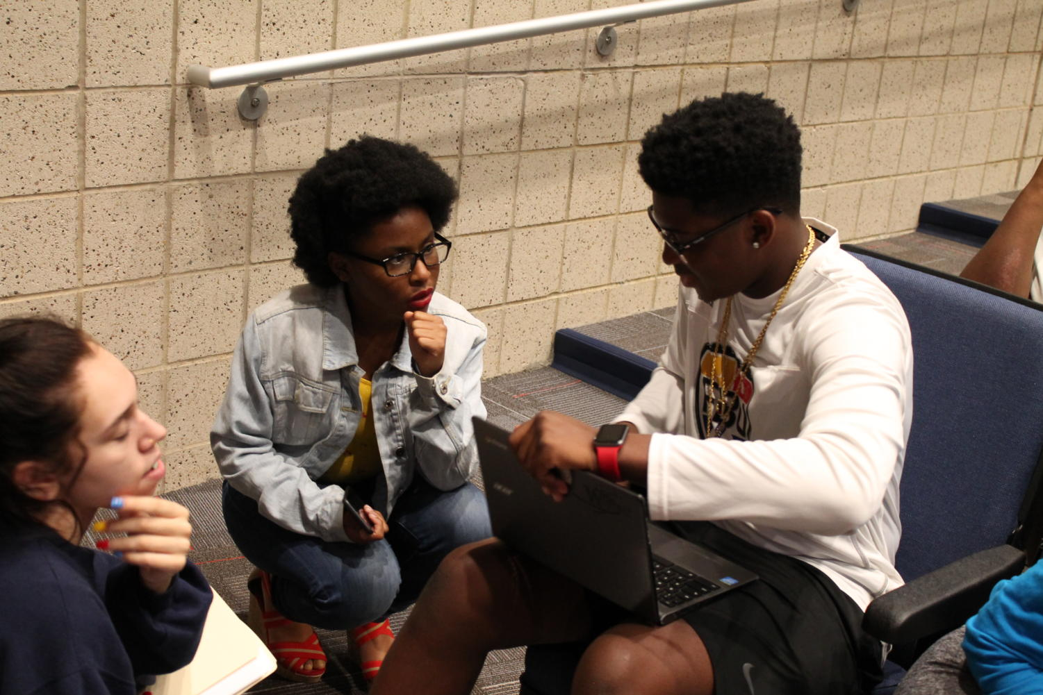 Juniors Grace Wilson, Aminah Lobster and Tai Williams collaborate before the meeting.