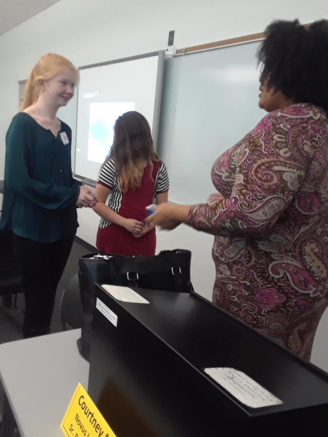 Freshman Maddie Sanderson asks Courtney Loveless Moore a question while she picked up her business card. Approximately 90 students from Computer Science Principles and the Intro to Engineering Design classes traveled to St. Charles Community College for a field trip.