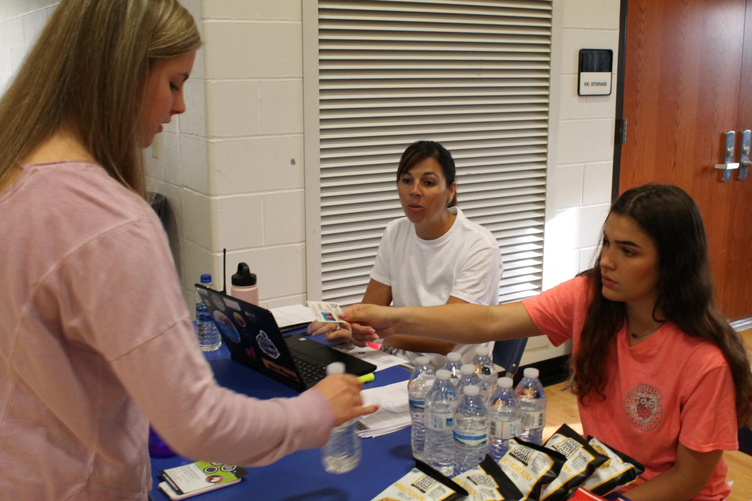 Junior Emily Gann checks in to donate blood with senior Laura Sanders and Mrs. Strathman.
