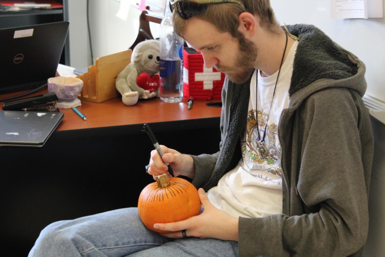 Senior Ian Beardslee paints his pumpkin in German Club.
