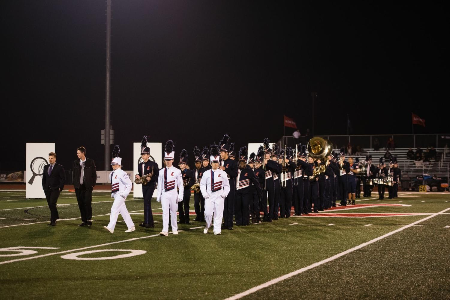 The band led by drum majors for their last show of the season.