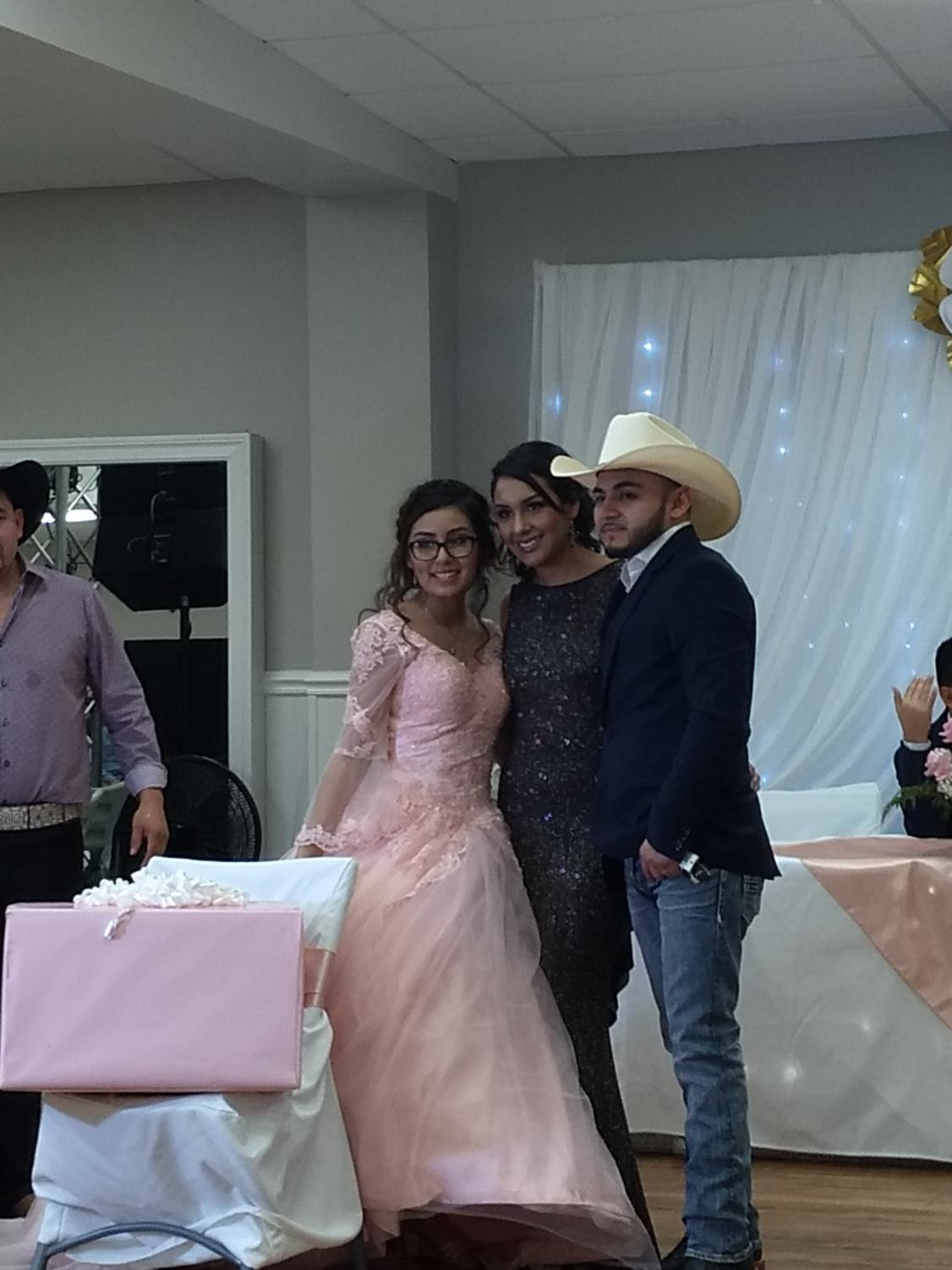 Alondra Mireles poses for a photo with her aunt and uncle after receiving a gift from them.