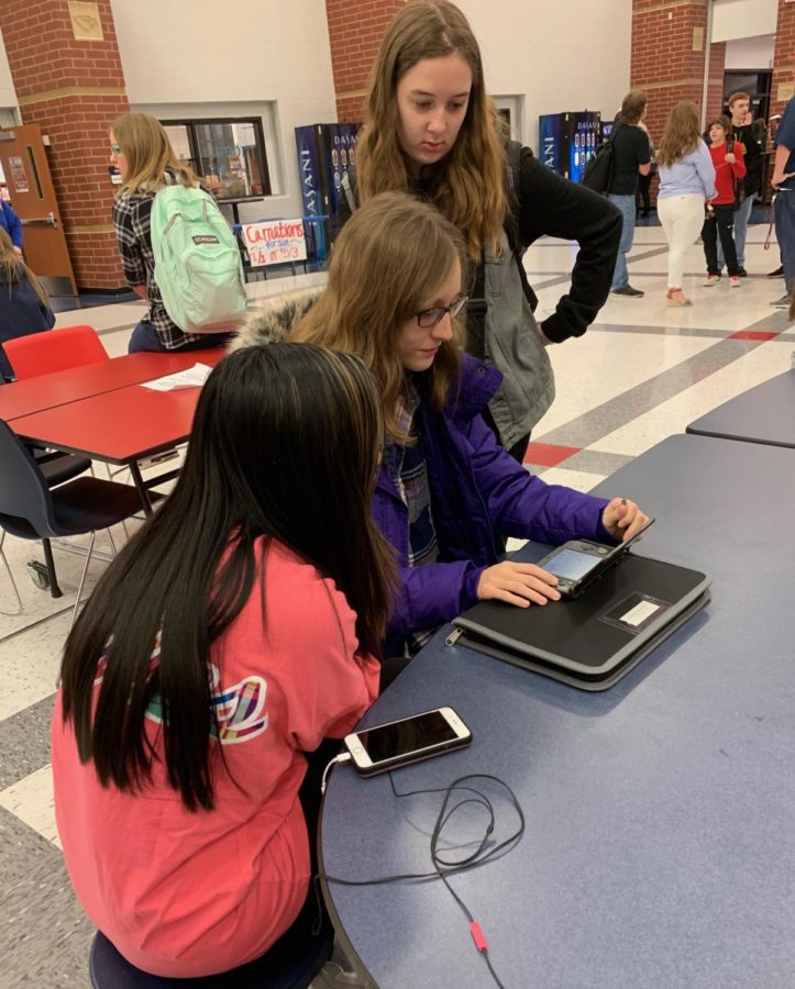 Freshmen Chynna Yeh, (left) Nora Wibbenmeyer, (middle) and Ashley Haberberger (right) play a game in the cafeteria before the first morning bell.