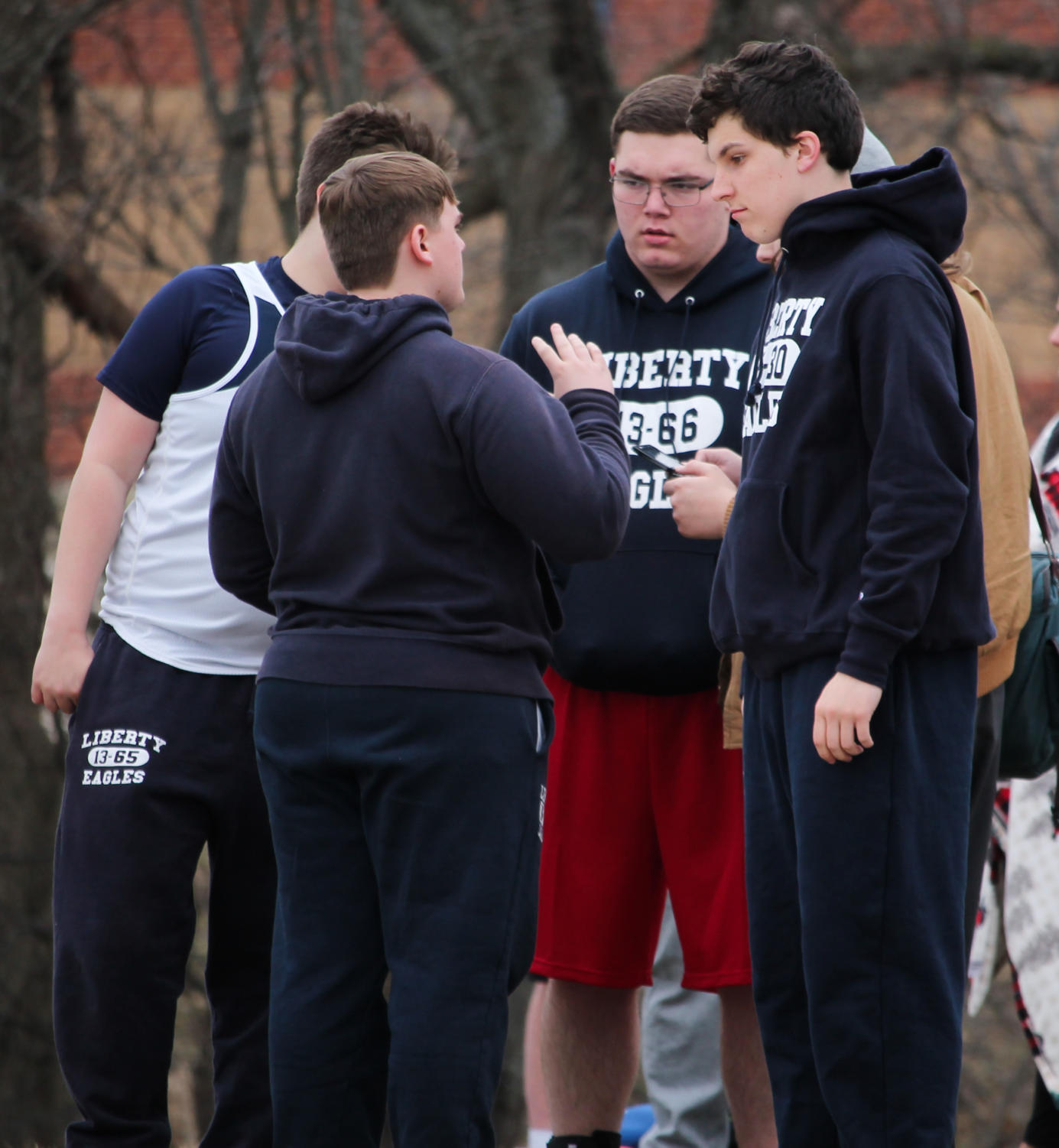 Blake Degner (middle) listens to newer throwers at a meet.