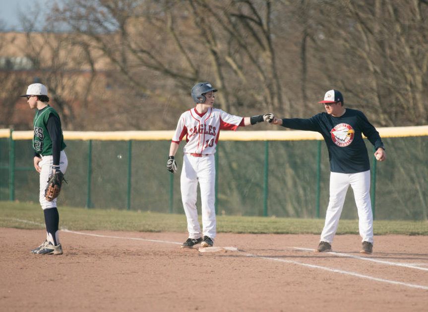Luke Linden is congratulated by coach Gonzales after Linden reached base successfully in a game earlier in the season against Timberland.