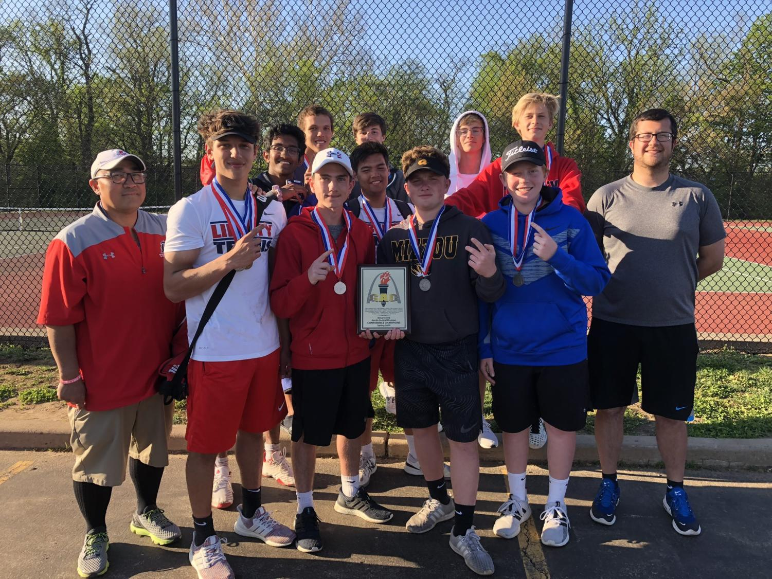 Varsity boys tennis gets together to celebrate their first conference title.