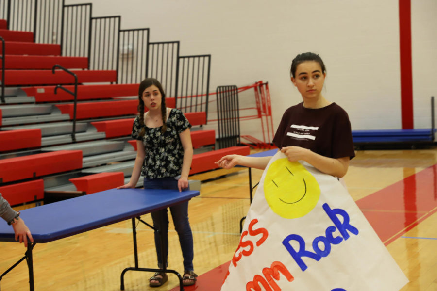 Sophomore Lizzie Kayser and junior Julia Bailey look for direction while setting up. Both have been student leaders in Come Together since its beginning.