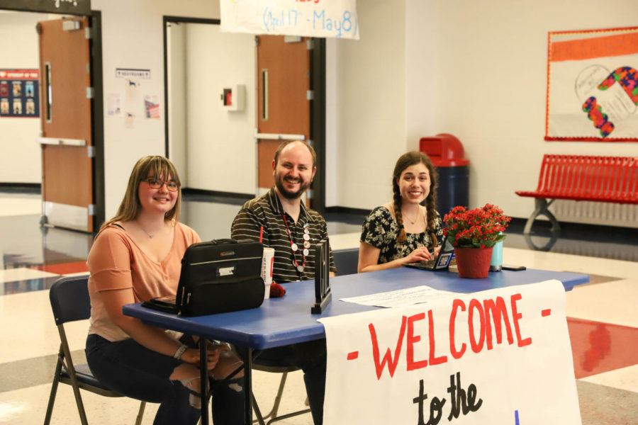 Senior Julie Jaggie, Mr. Eversole and sophomore Lizzie Kayser greet people as they enter the De-stress Event.