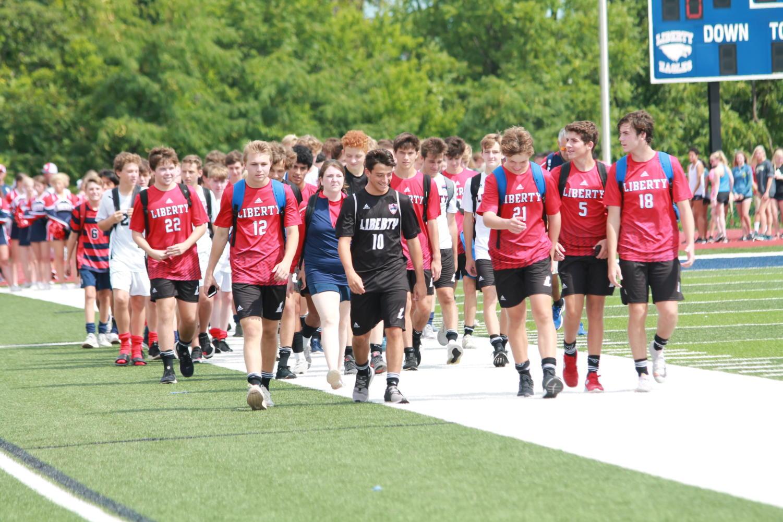 Soccer+athletes+make+their+way+along+during+the+parade+of+athletes.