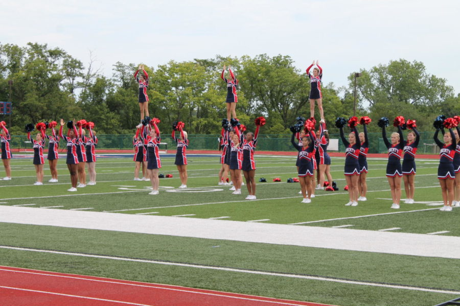 Cheerleaders do an extension during their routine.