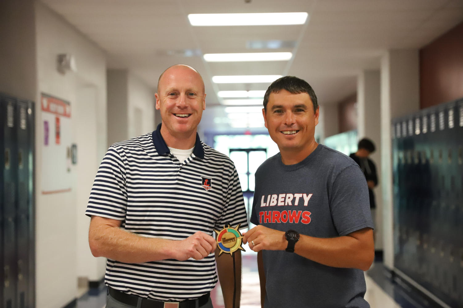 Mr. Eldredge (left) and Mr. Glavin (right) pose with the medal they won for the race.