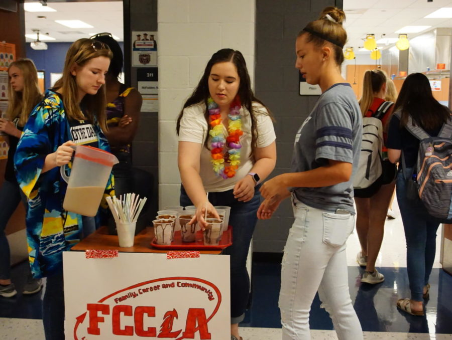 FCCLA members Audrey Champers (left) and Katelyn Yoder (middle) setting up the coffee stand