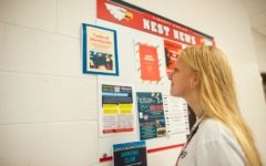 Sophomore Dori Earle checks out tasting event flyer displayed in the 400 hallway.