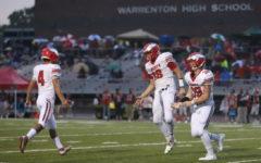 Blake Seaton (18) celebrates a touchdown with teammates Josh Paubel (4) and Zach Dotson (39) in the team's 28-14 win against Warrenton.