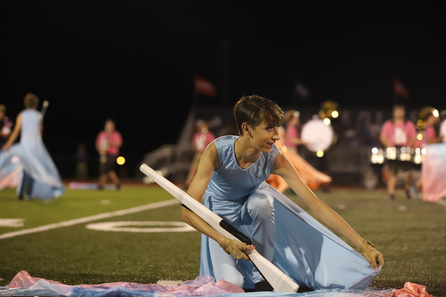 Junior Eric Welker gets ready to spin rifle during halftime at a football game.
