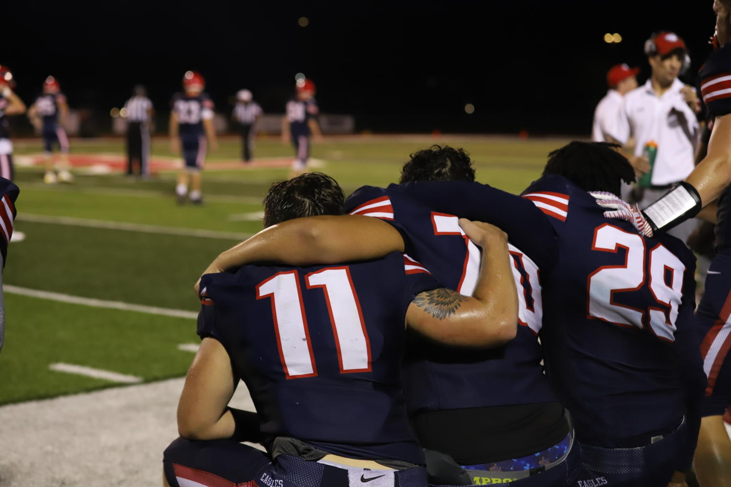 Seniors Cooper Terrell, Gabe Gonzalez and Jeremiah Williams embrace at the end of the senior night football game.