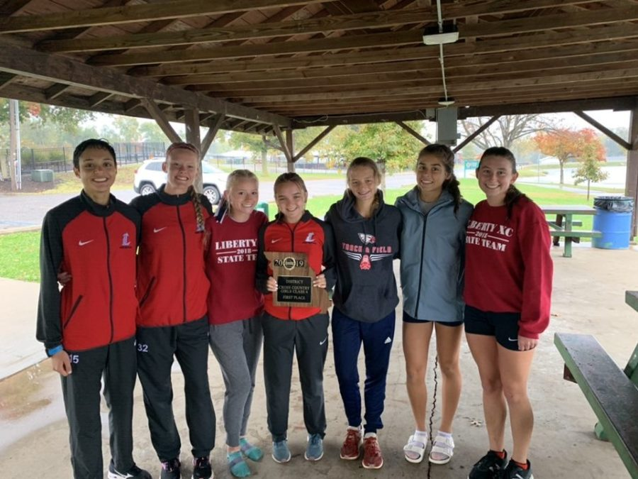 The+girls+cross+country+team+poses+with+their+first+place+district+plaque.