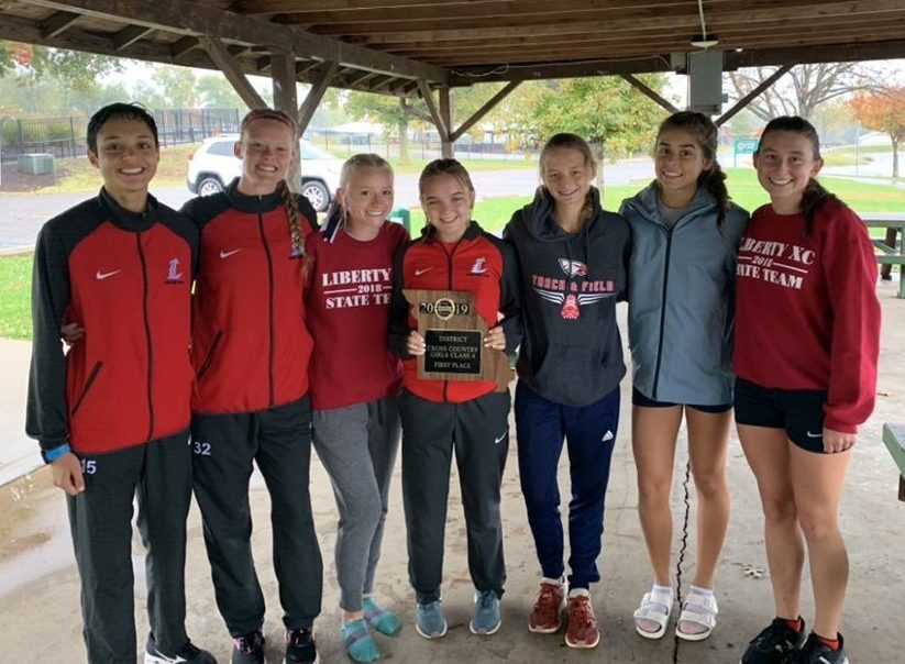 The girls cross country team poses with their first place district plaque.