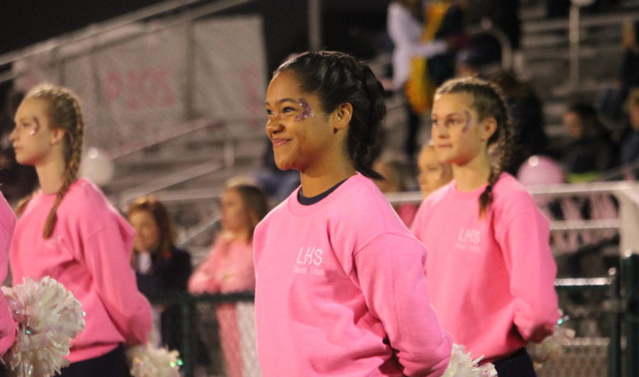 Charity Edney stands with the dance team, watching the Pink Night festivities.