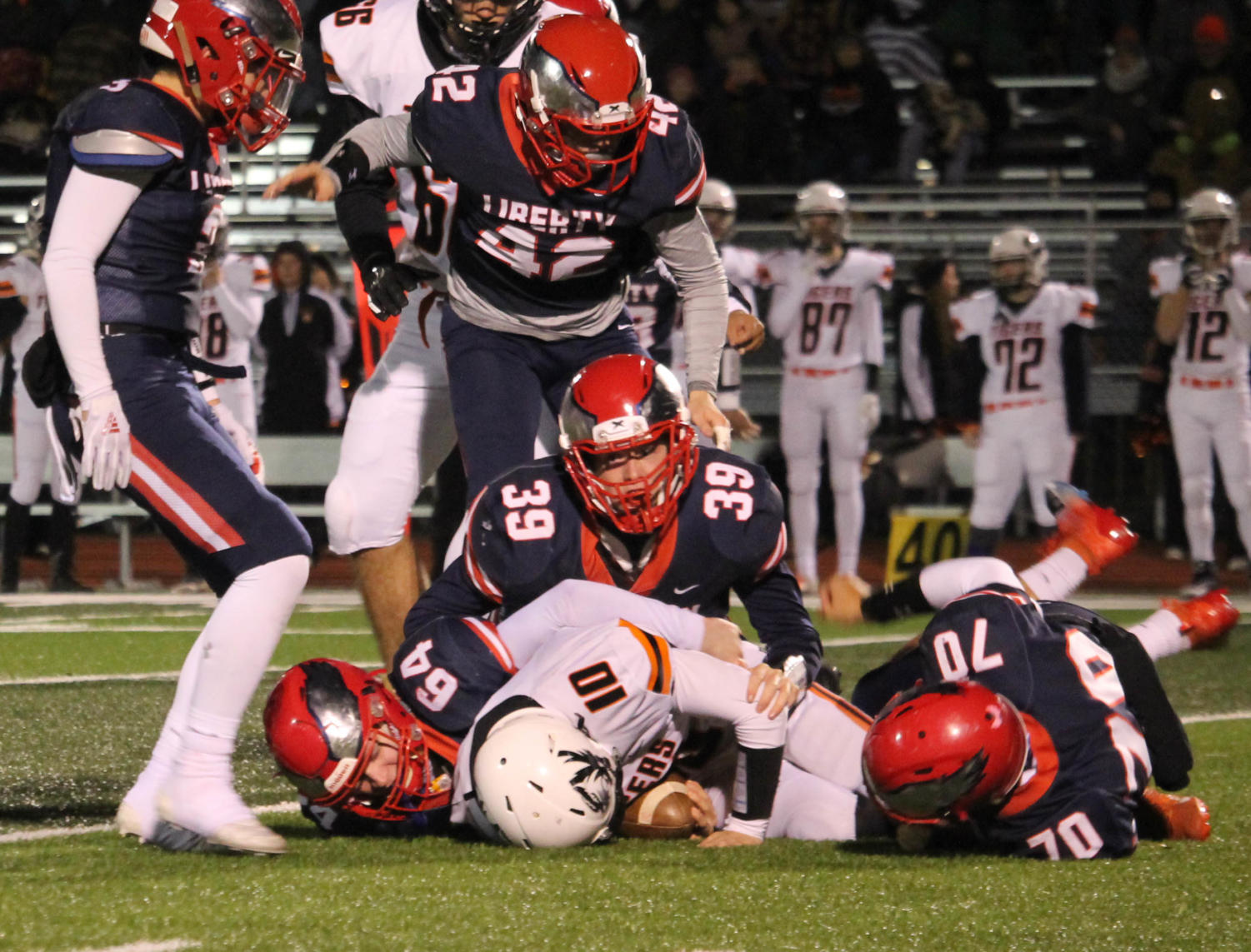 Zach Dotson (39), Anthony Tavolacci (64) and Gabe Gonzalez (70) bring down the Kirksville ball carrier during Liberty's victory in the district semifinal game.