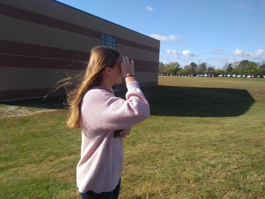 Senior Paige Eikel looks into color blind glasses to see certain colors for the first time.