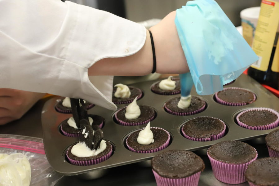 Student ices chocolate cupcakes to place Oreo bats on top.
