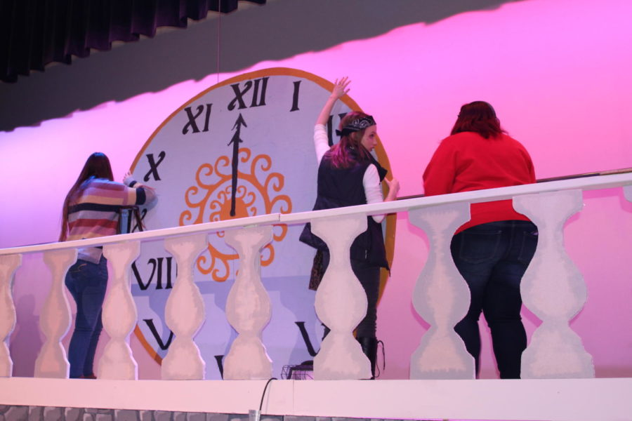 Brianna Dierks, Audrie Helms and Madison Haynes hold up the giant clock.