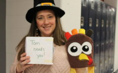 Mrs. T.O. stands in the hallway wearing her pilgrim hat asking for change for the turkey drive.