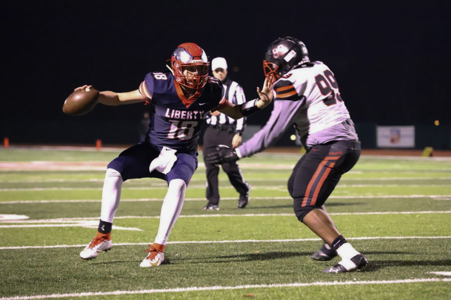Quarterback Blake Seaton eludes a tackler during the district championship game. Seaton passed for two touchdowns and ran for another TD score.