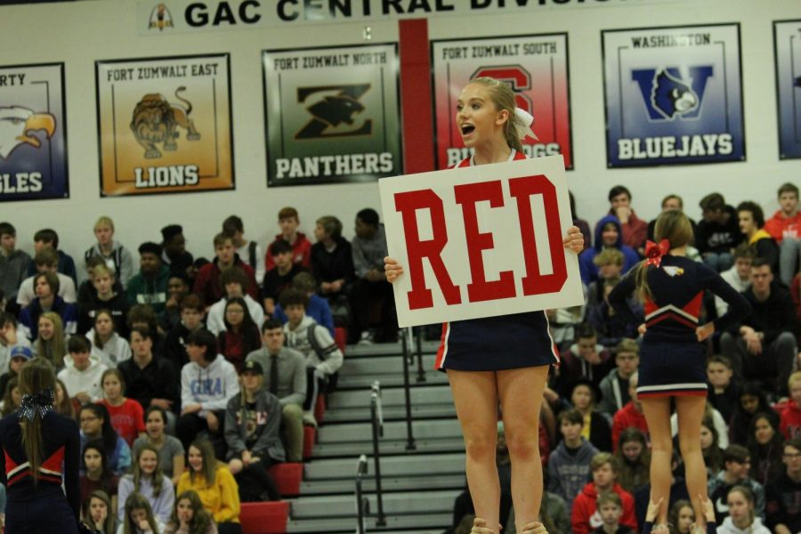 Flyer+and+junior+Bailey+Crow+holds+up+a+%22RED%22+sign+during+the+cheer+routine+at+the+pep+assembly.