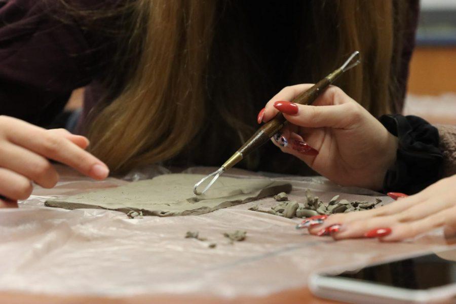 Two freshmen work on their relief sculptures in art fundamentals.