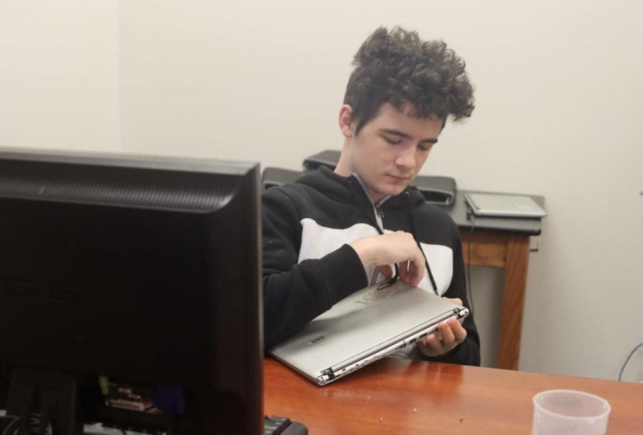 Junior Pierce Polydys assesses a malfunctioning Chromebook while working in the lab.