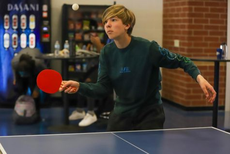 Freshman Schrader Ludwig serves the ping pong ball to his opponent.