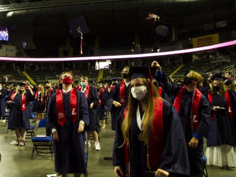 Graduates throw their caps into the air and celebrate at the end of the commencement ceremony.