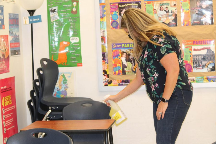 Madame Farrelly sprays and wipes down each desk between classes.