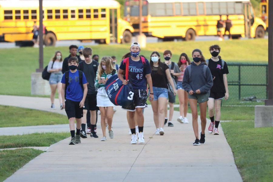 Students walk from the bus to the school for the first time this year.