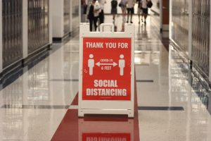 Bright red signs can be seen throughout every major hallway, requesting students and staff to socially distance.