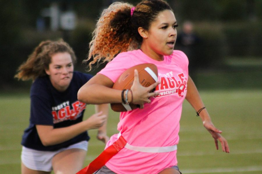 Eve Shelton (12) sprints towards the end zone while Piper Abernathy (11) races to pull her flag.