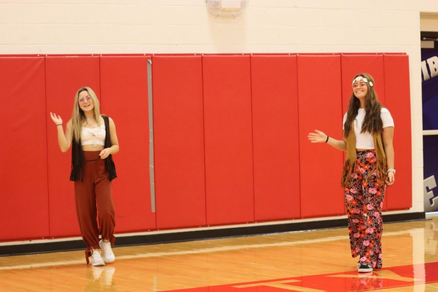 Tess Roberts (left) and Molly Marino (right) kick off the virtual assembly rocking their 70s outfits.