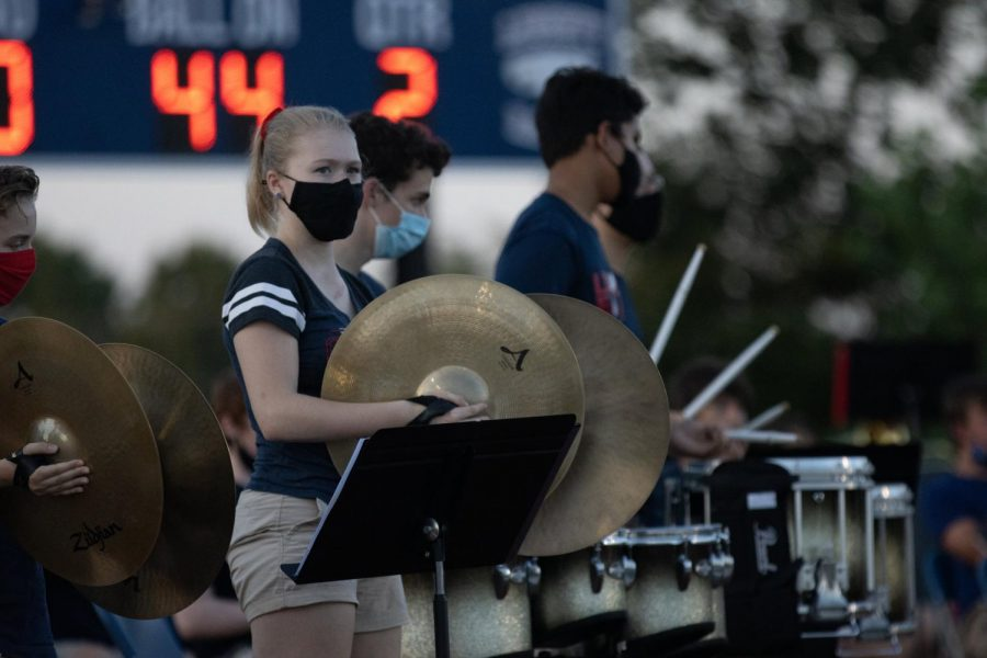 Christina Bertenshaw plays the cymbals during the second quarter of the first football game of the season.