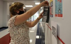 Secretary of Key Club Elizabeth Hamby hangs up a voting drive QR code.
