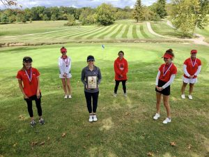 The varsity golf team, newly conference champions, stands on the course after their win.